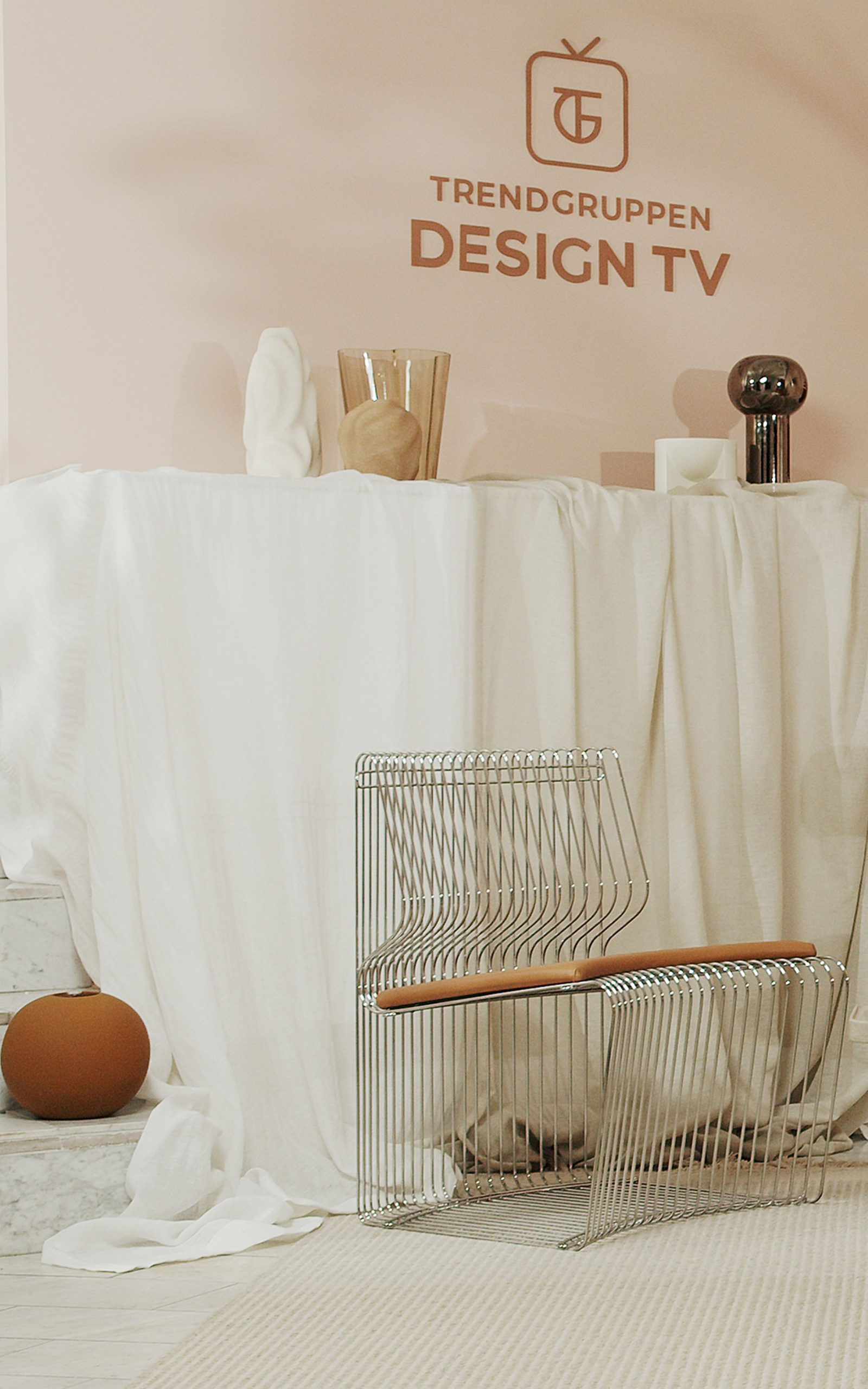 A steel chair and glass and ceramic vases on TV set
