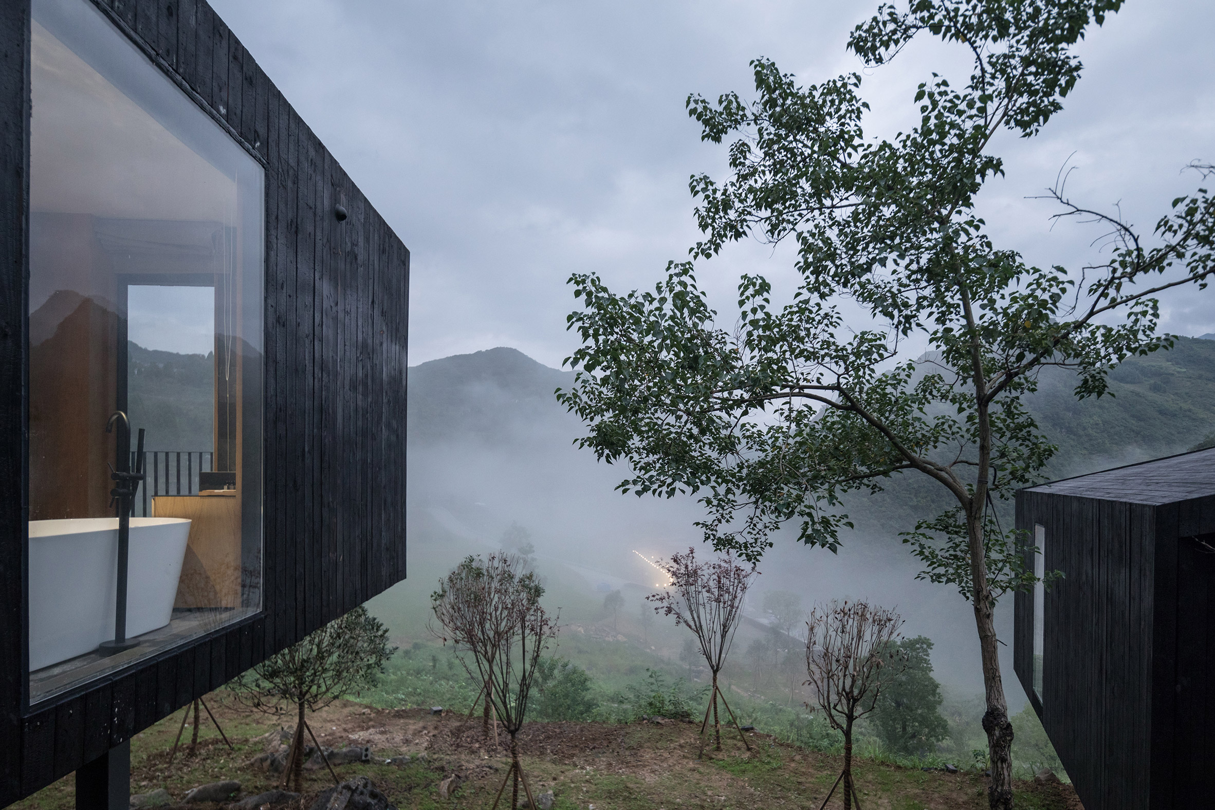 Blackened wood cabins raised above the ground
