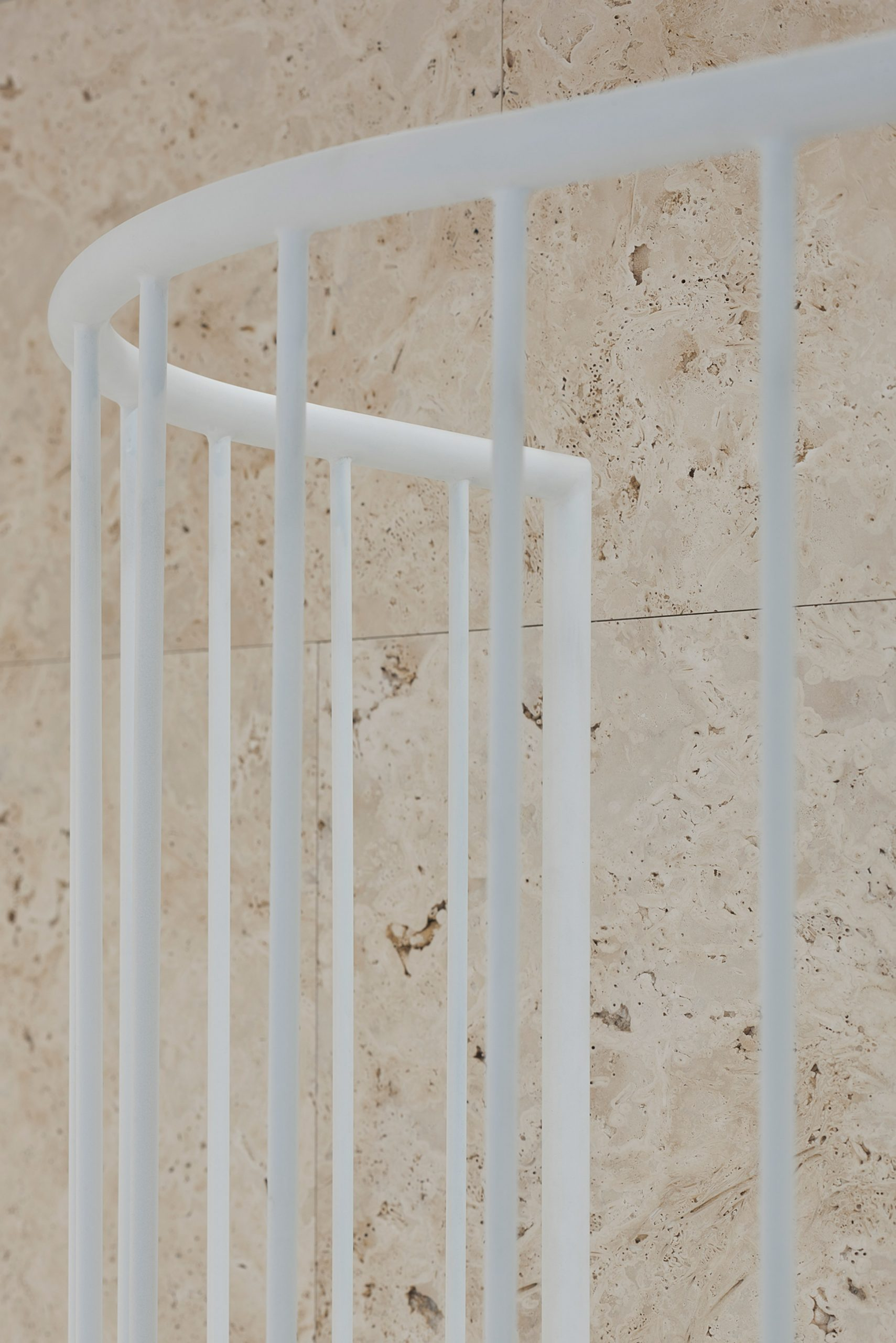 Travertine wall and steel staircase banister in Vilnius apartment by 2XJ