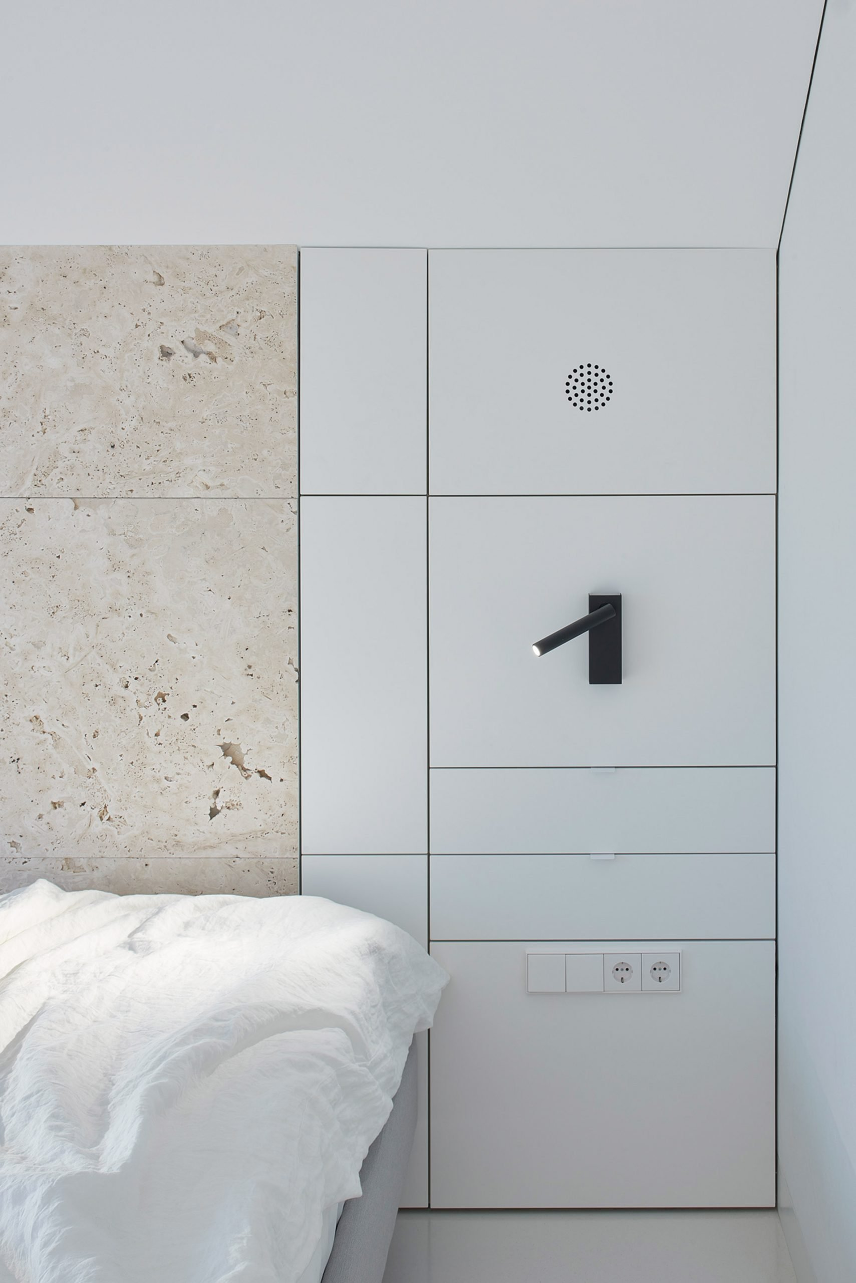 Bedroom with built-in lighting, storage and travertine wall in Greetings from Rome apartment