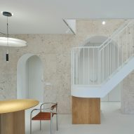 Arched travertine wall carves up Greetings From Rome apartment by 2XJ