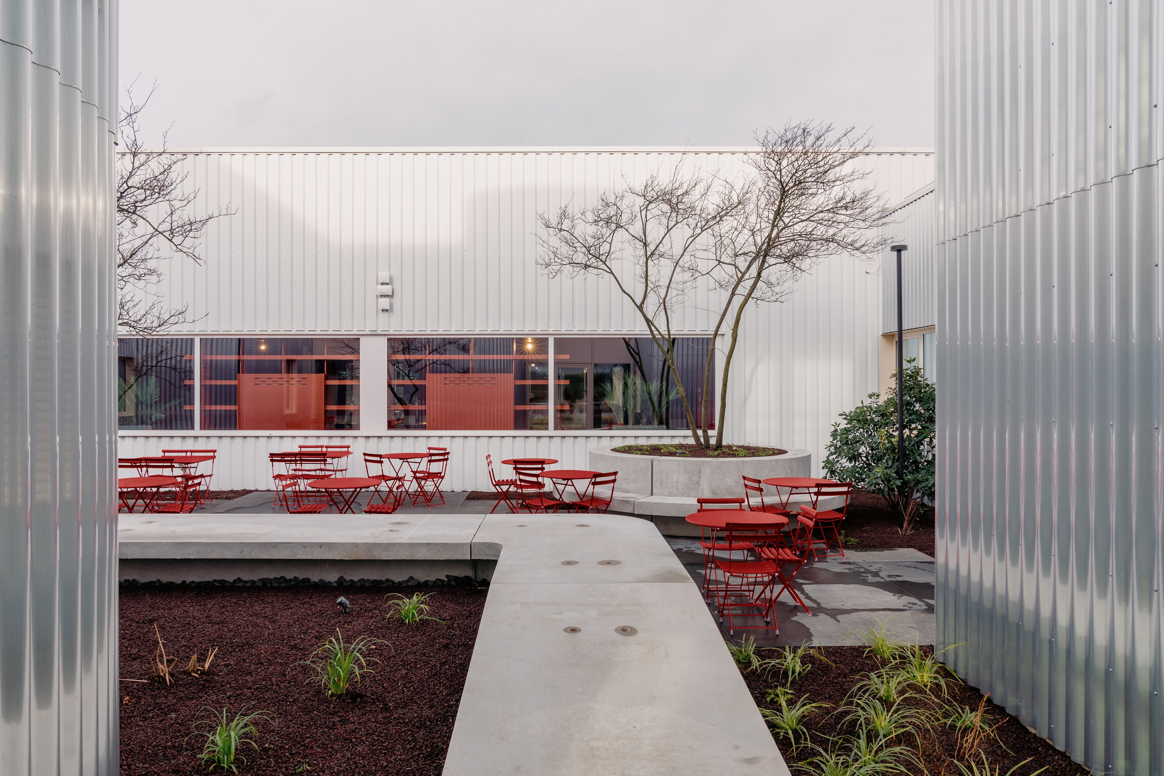 The courtyard has red furniture and wild landscaping by Studio Anton Hendrik Denys