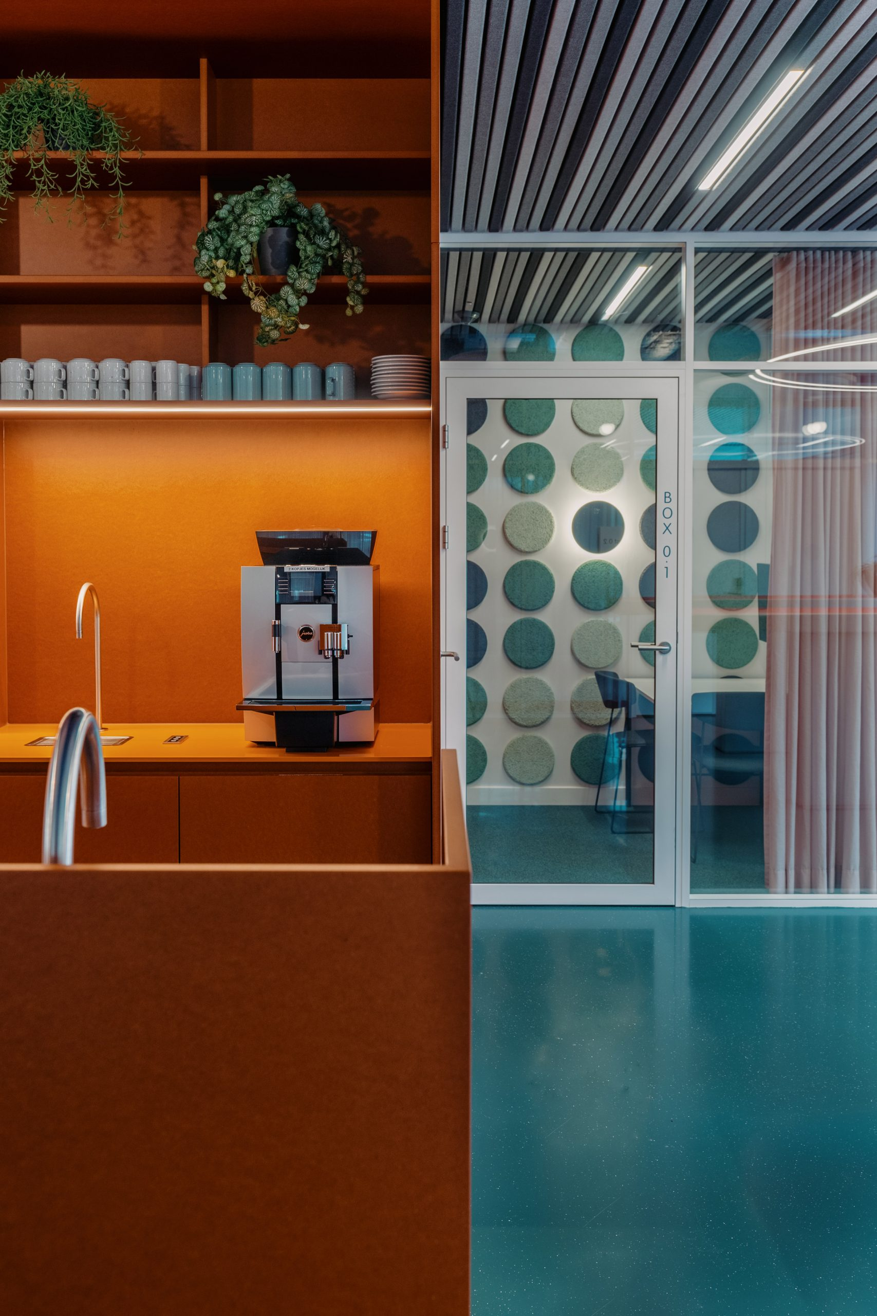An orange kitchen with silver hardware sits atop green flooring