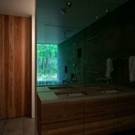 The bathroom uses wood finishes