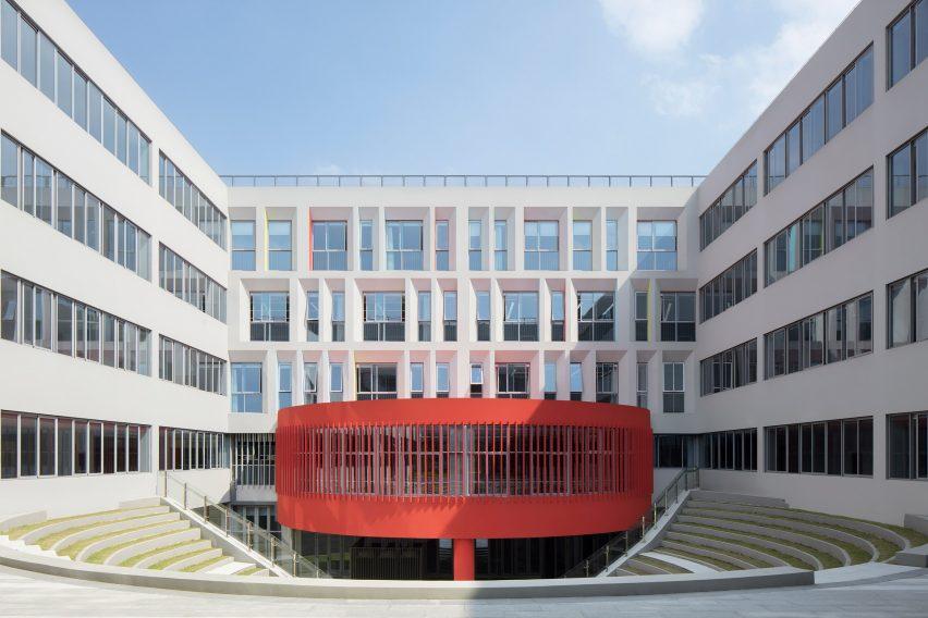 A circular red form sits atop a sunken courtyard