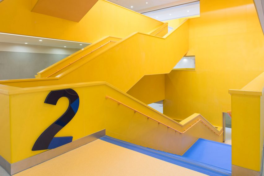 Yellow staircase is decorated with large numbers