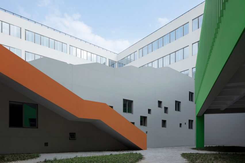Orange staircase contrasts against a green library