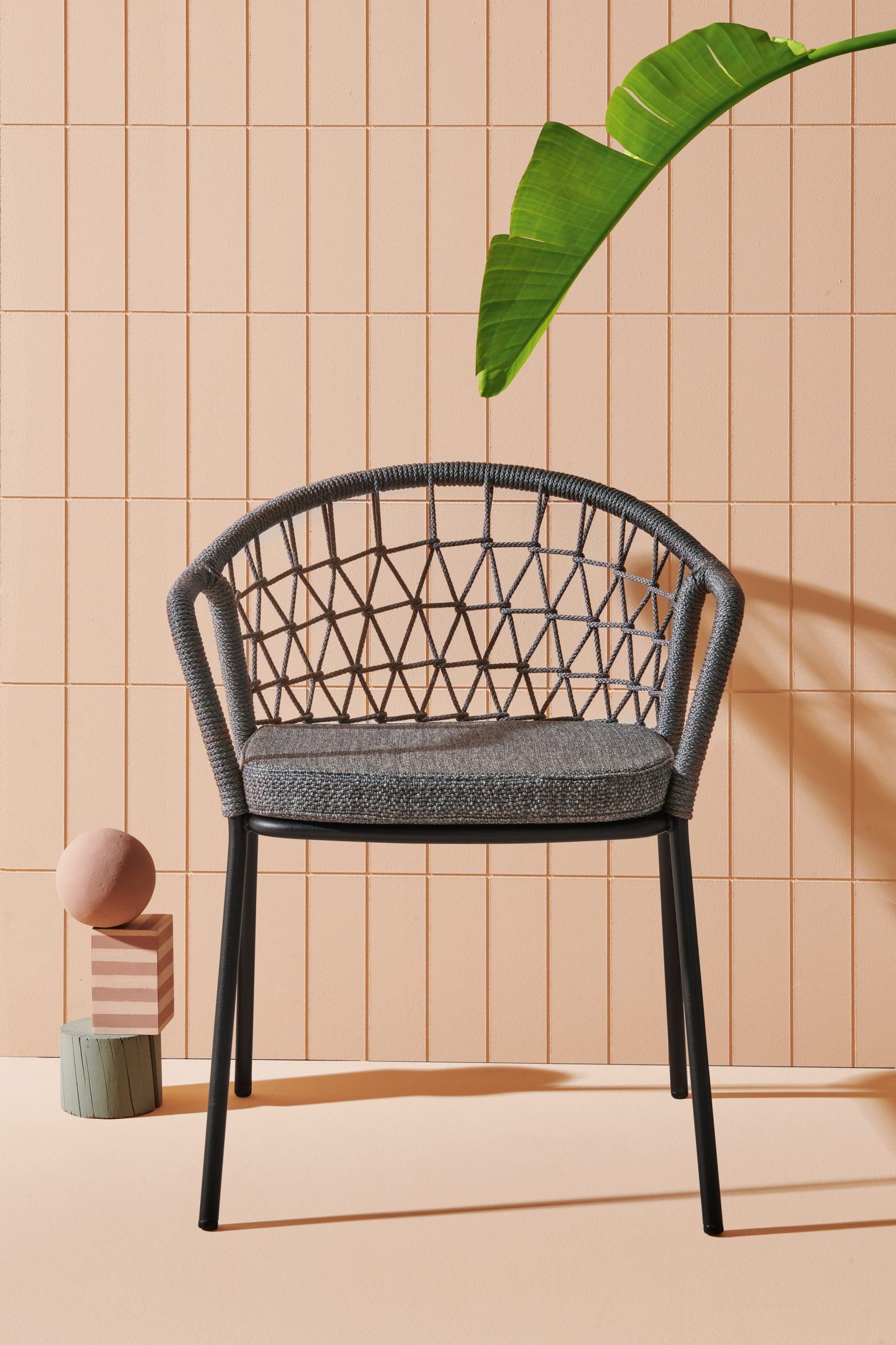 Grey chair with a hand woven backrest by CMP Design