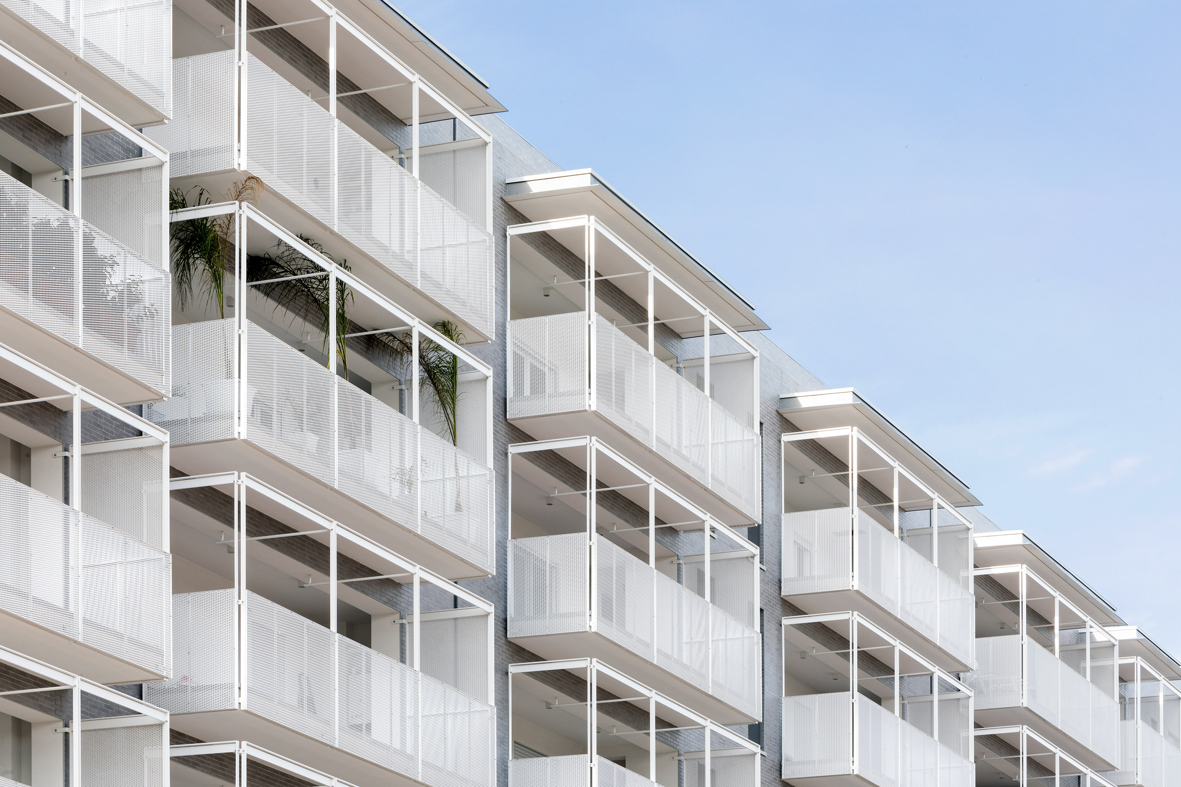 White perforated balconies protrude from the brick