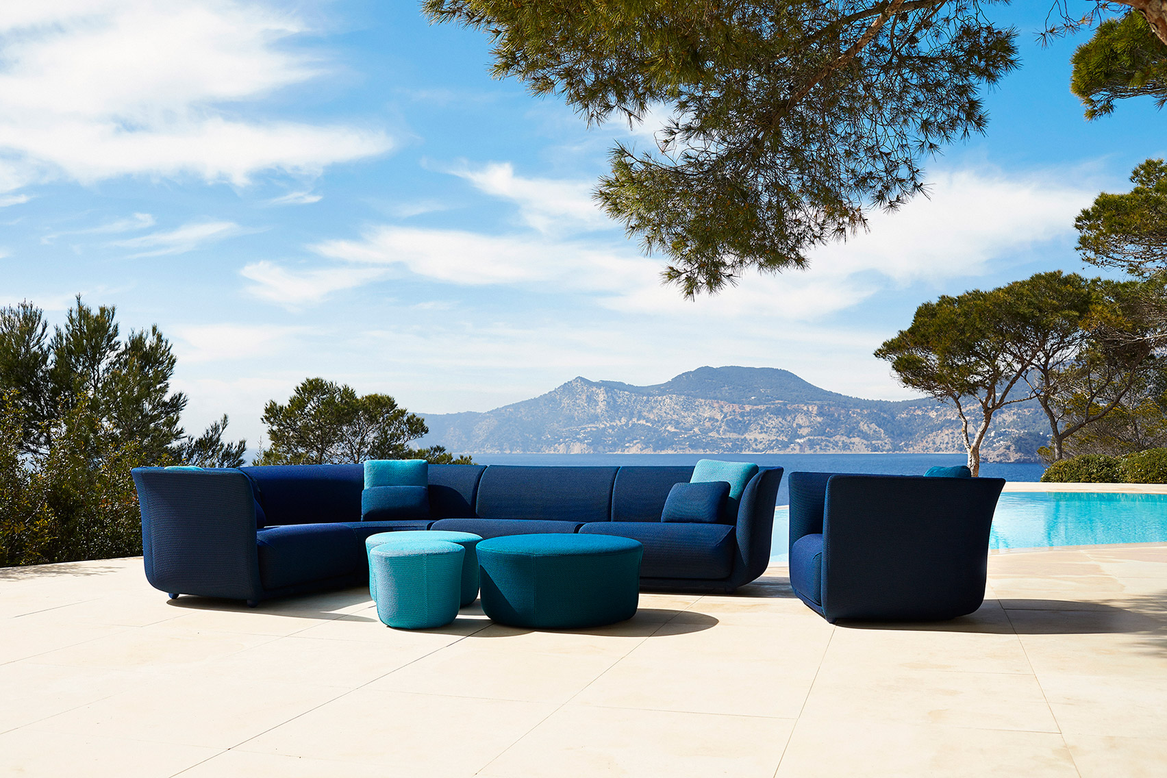 Curved modular sofa accompanied by lounge chair and pouffe
