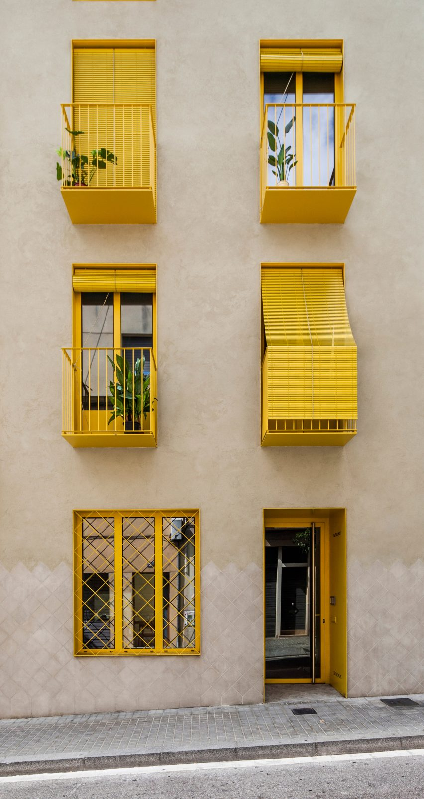 Yellow features contrast with the stucco by Anna & Eugeni Bach