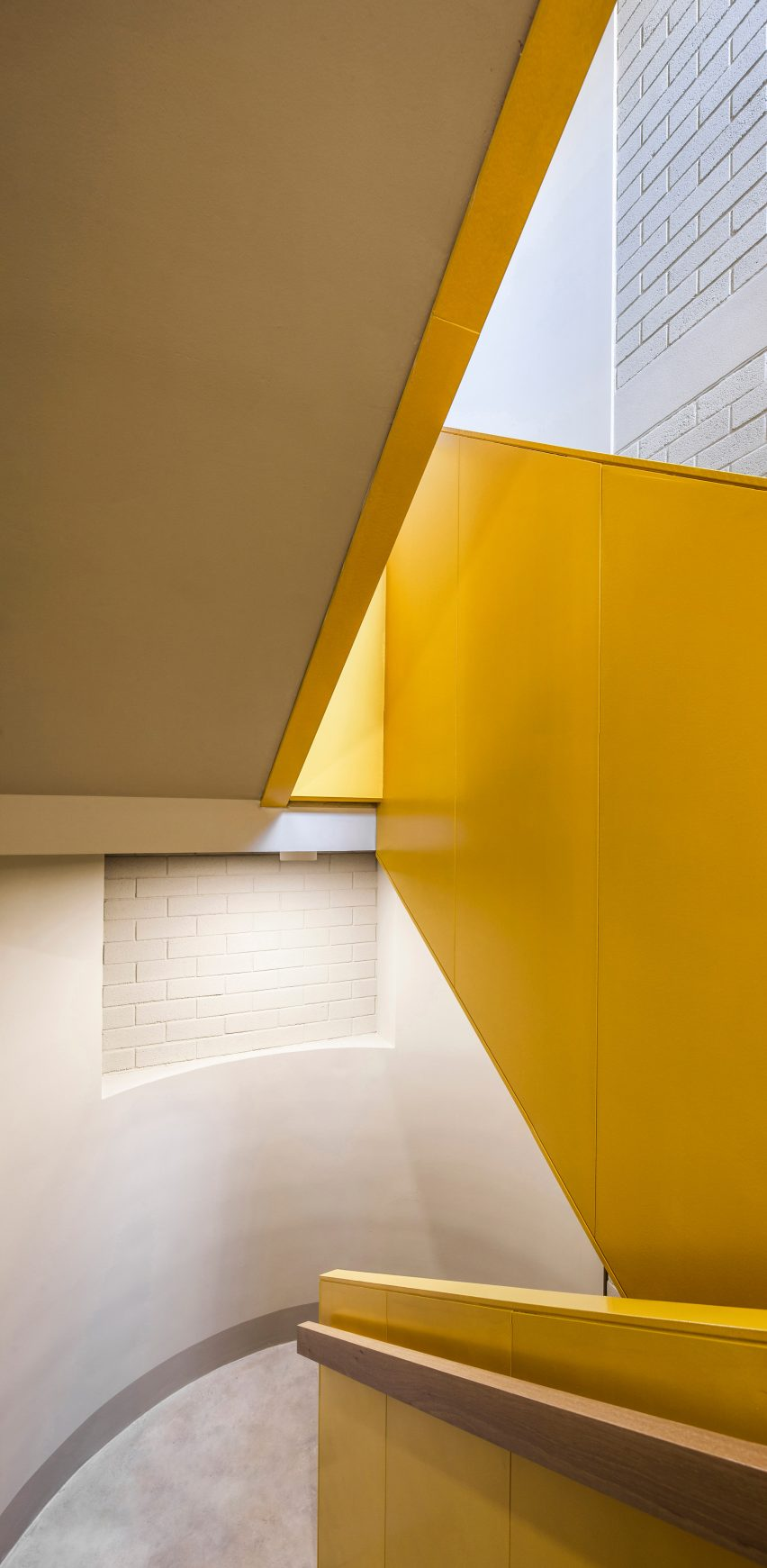 A yellow staircase contrasts against white walls