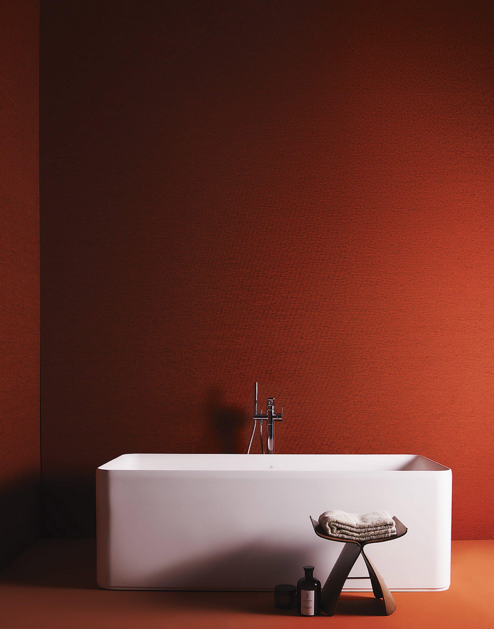 A warm orange bathroom with a freestanding white bath