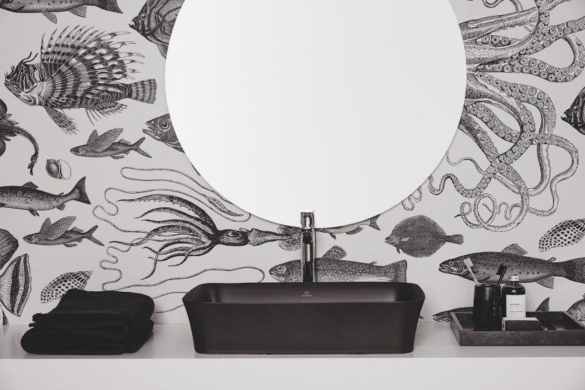 A monochromatic bathroom with a black washbasin