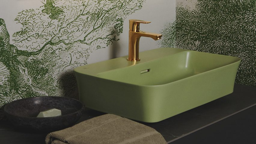 A bathroom with a sage green sink and brass tap