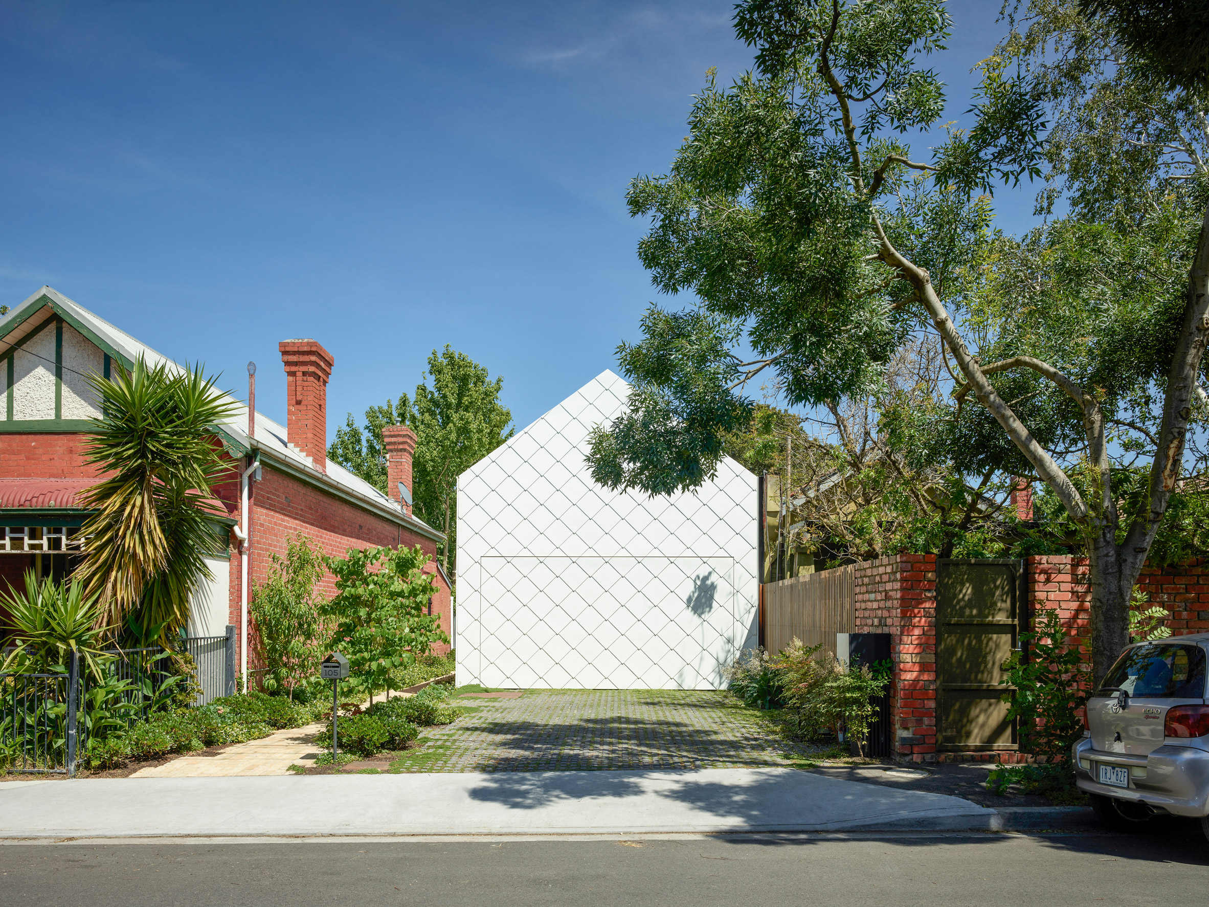 White shingled facade amongst residential buildings by Austin Maynard Architects