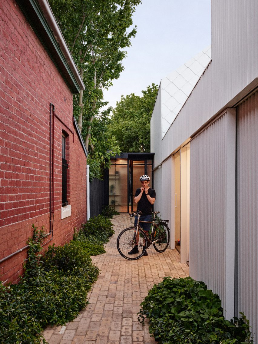 Brick passageway beside the garage and neighbouring home by Austin Maynard Architects