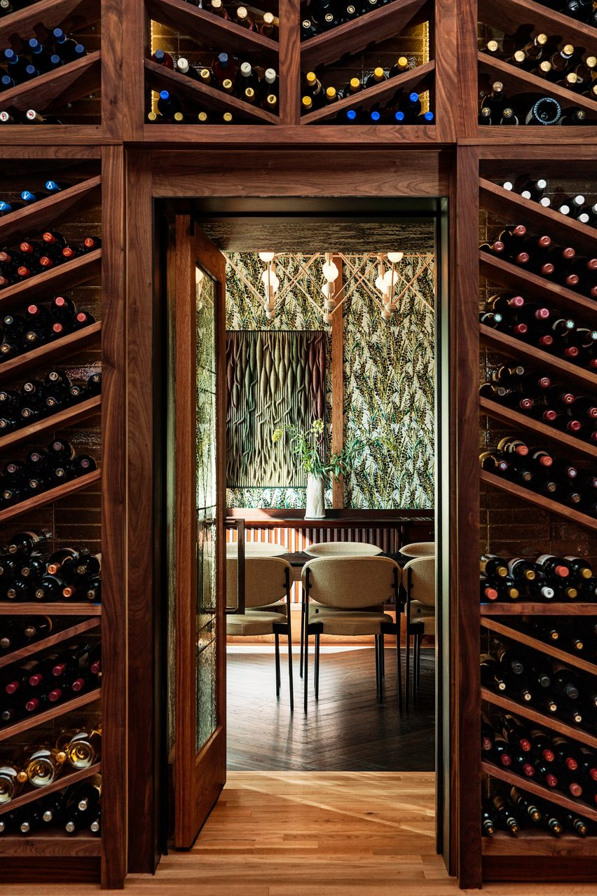 Wall of wine racks and botanical wallpaper in Peacock restaurank
