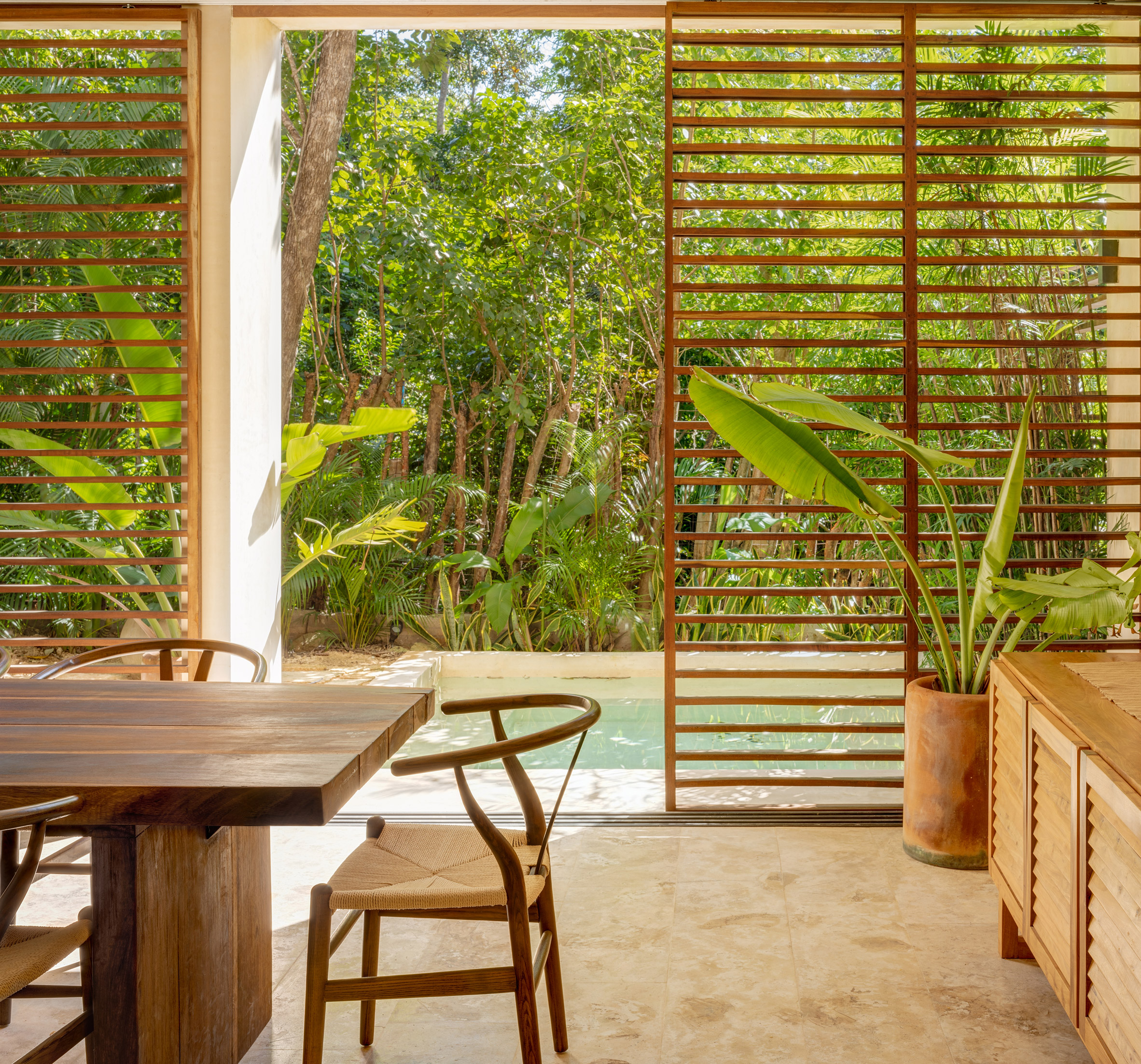 Wooden louvres and swimming pool of BAI-HA holiday complex in Tulum