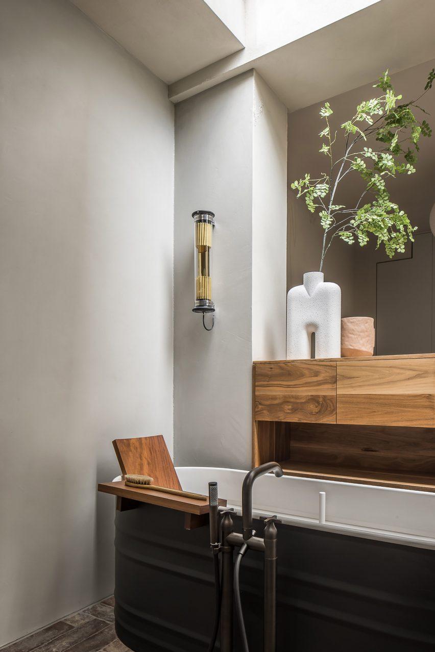 Free-standing black tin bath in bathroom