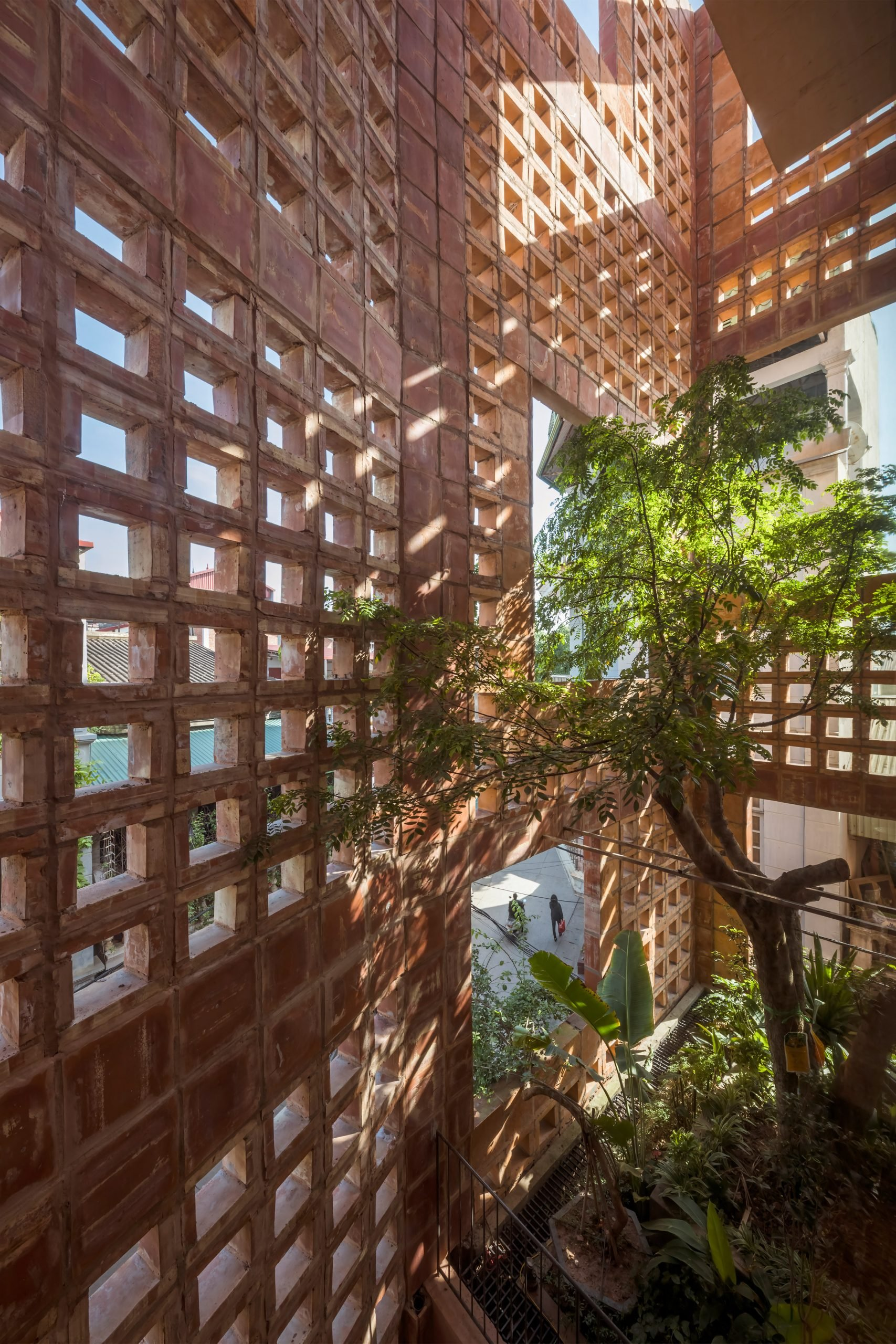 Green spaces fill the space between the wall and home by Vo Trong Nghia Architects