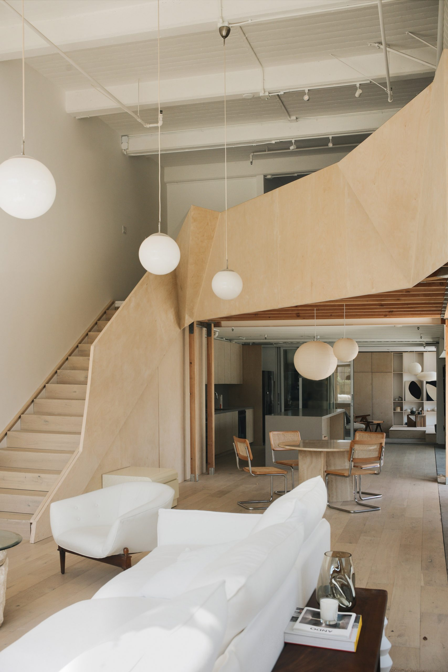 Sculptural wooden staircase and mezzanine by OWIU Studio