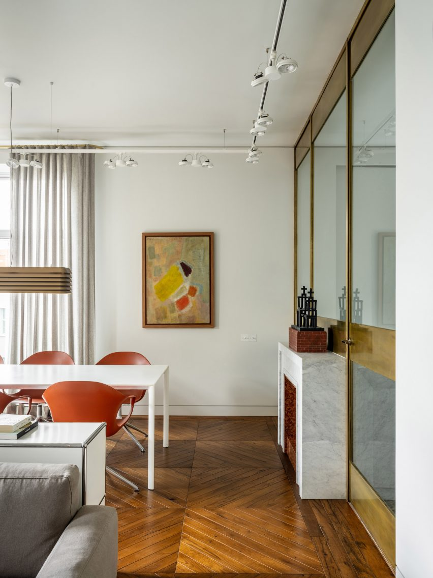 Dining room and brass-framed glass partition wall in Moscow apartment