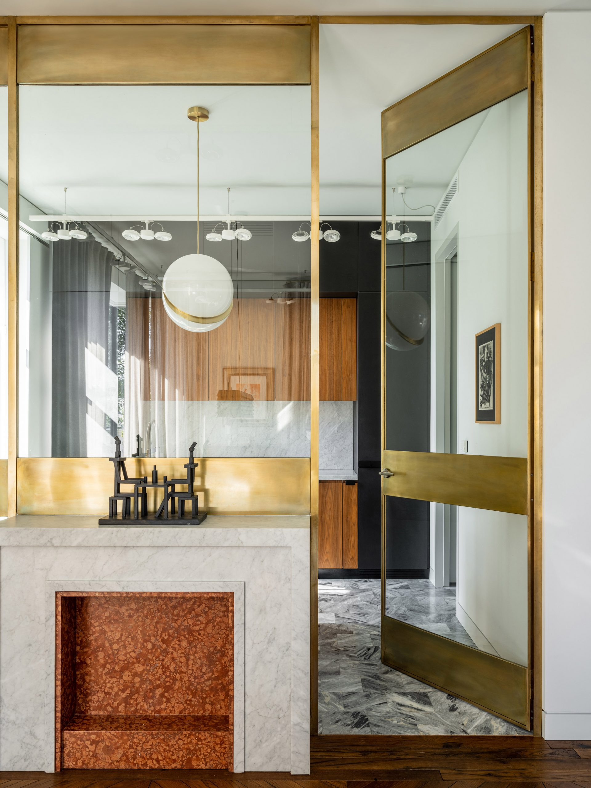 Brass-framed glass partition wall with marble mantlepiece in Moskow apartment
