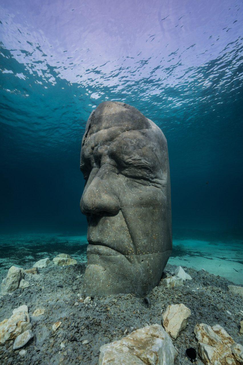 A cement sculpture of a human head under water
