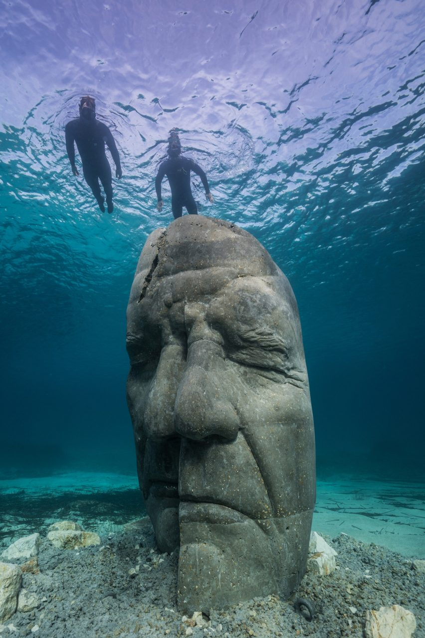 Two snorkelers observing an underwater sculpture of a human face