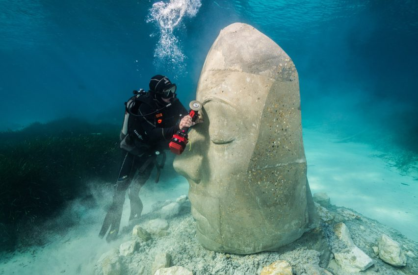 A diver carving a underwater sculpture of a human face