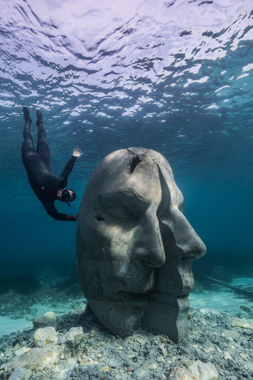 A snorkeler alongside an underwater sculpture