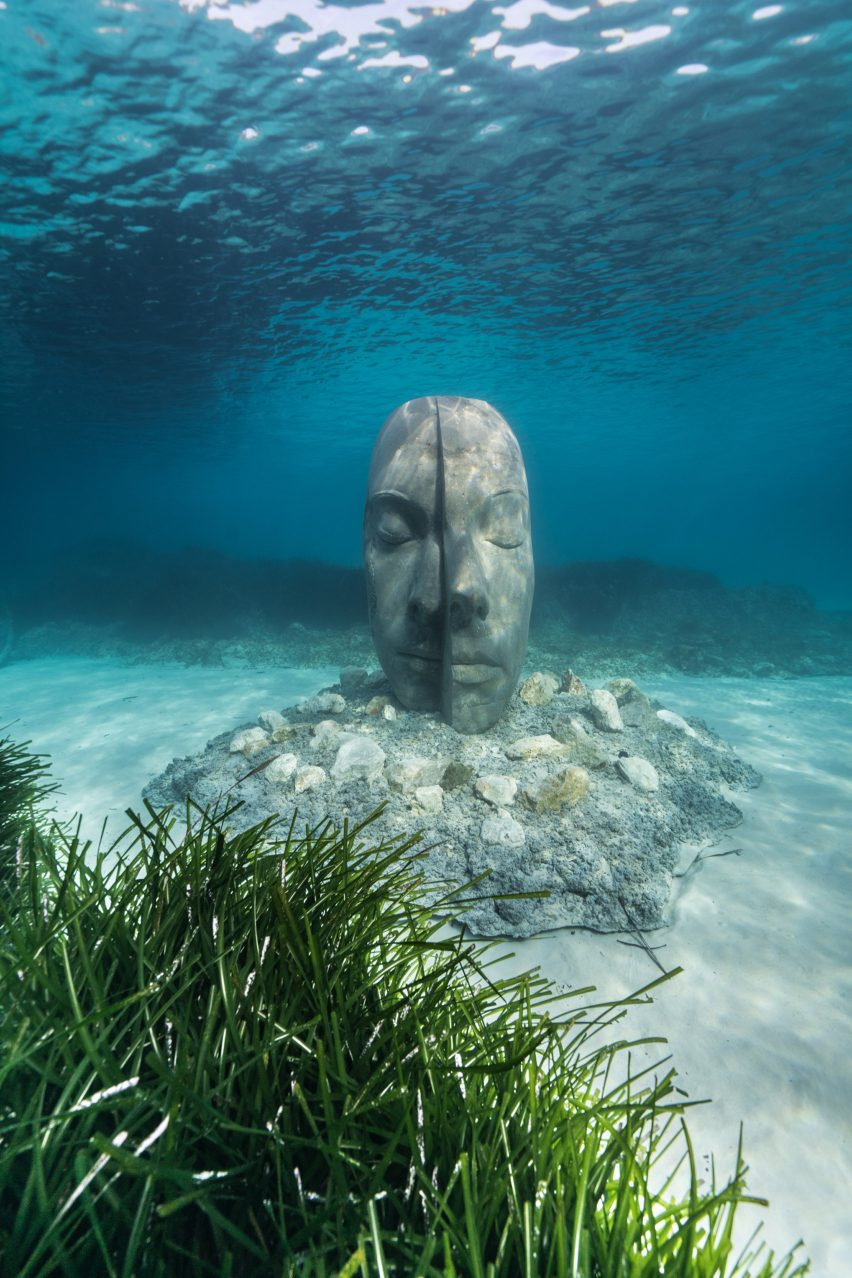 A sculpture of a human head submerged under water