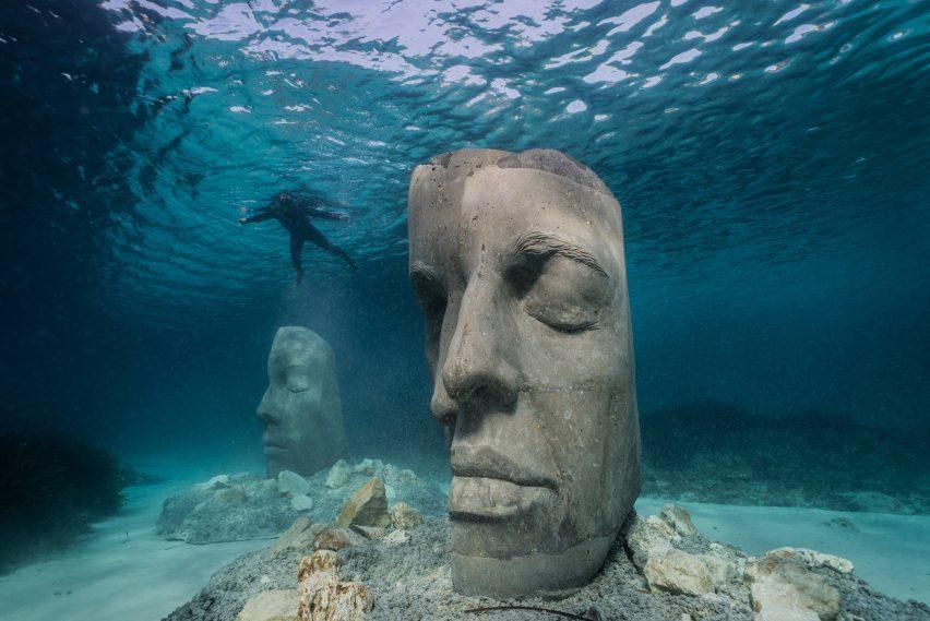 A snorkeler observing two underwater sculptures