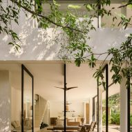 The house's large windows blend interior and exterior spaces