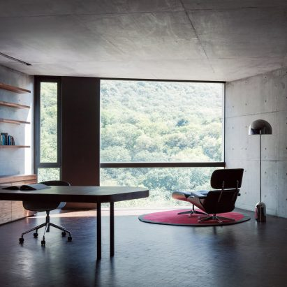 Home office with concrete walls and large window