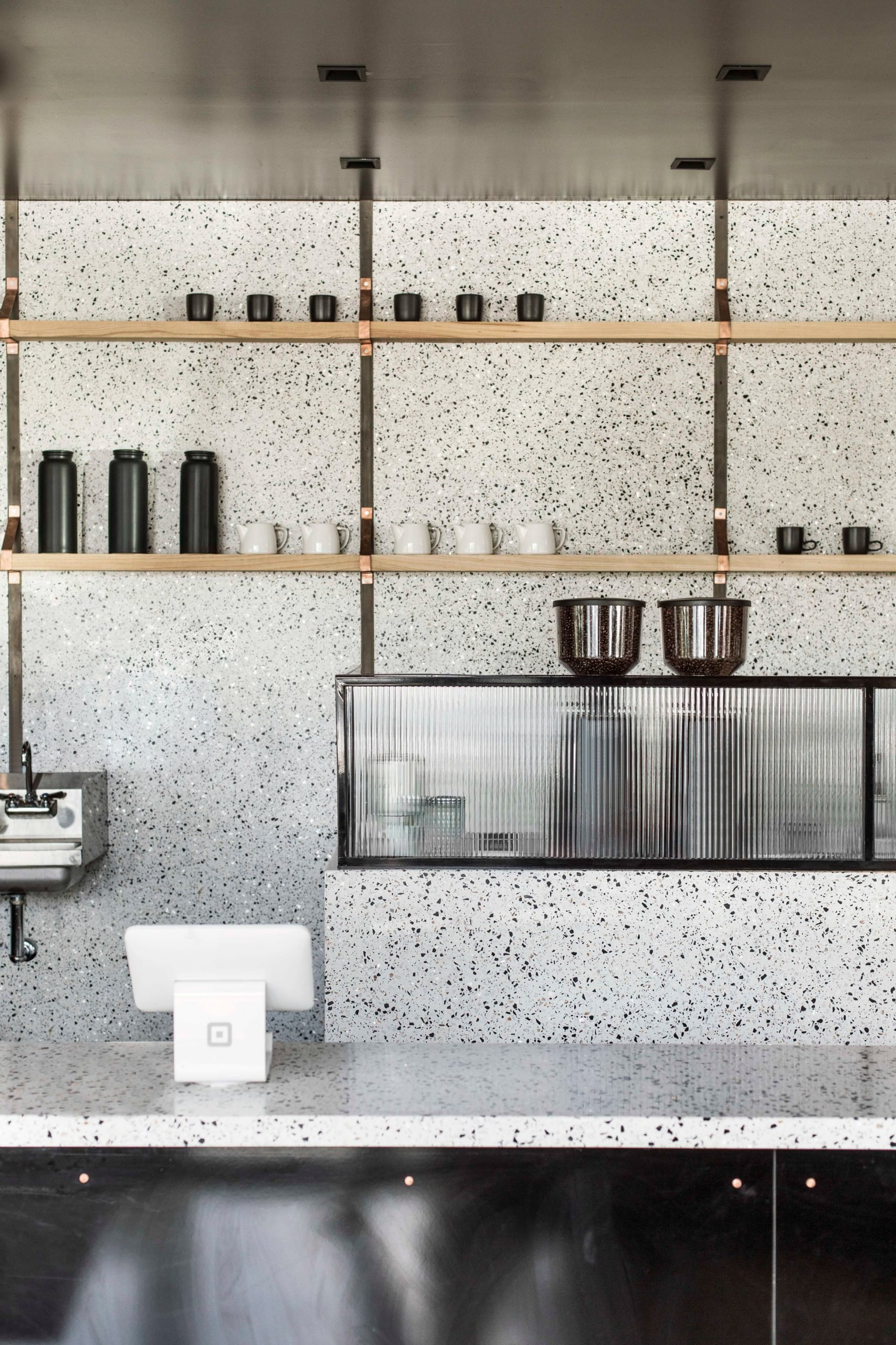 Terrazzo coffee bar with wooden shelves