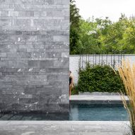 A swimming pool outside a private stone spa