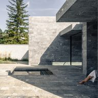 The exterior of a monolithic stone spa by Smartvoll