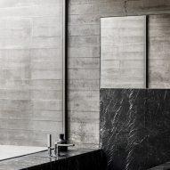 A concrete bathroom with a black stone bathtub