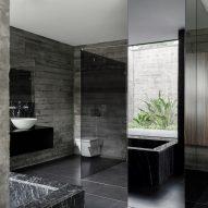 A concrete bathroom with black floor tiles