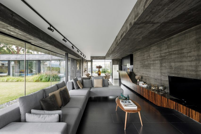 A concrete and glass-walled living room of Cork Oak House