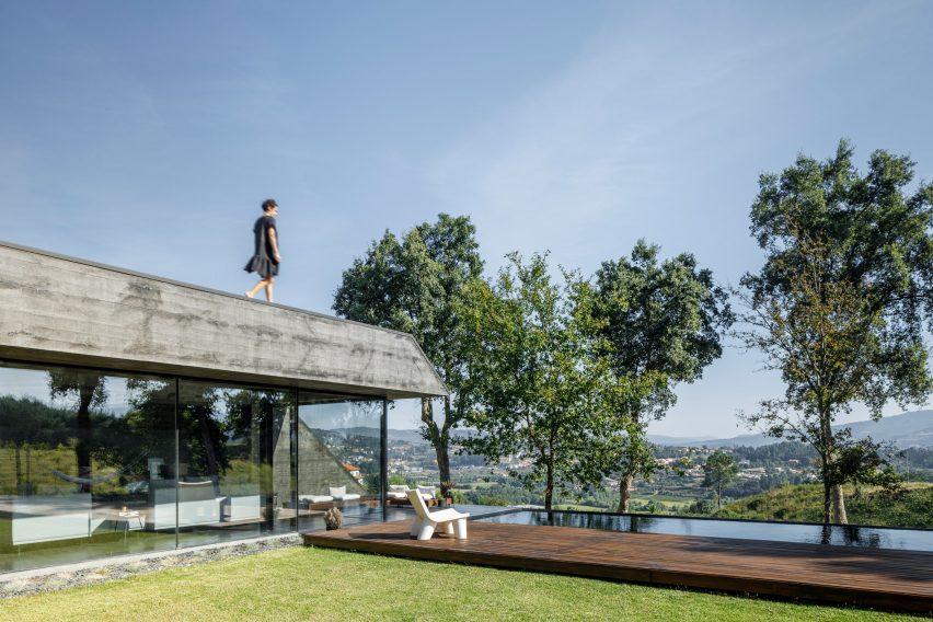 A hilltop concrete house with a roof terrace