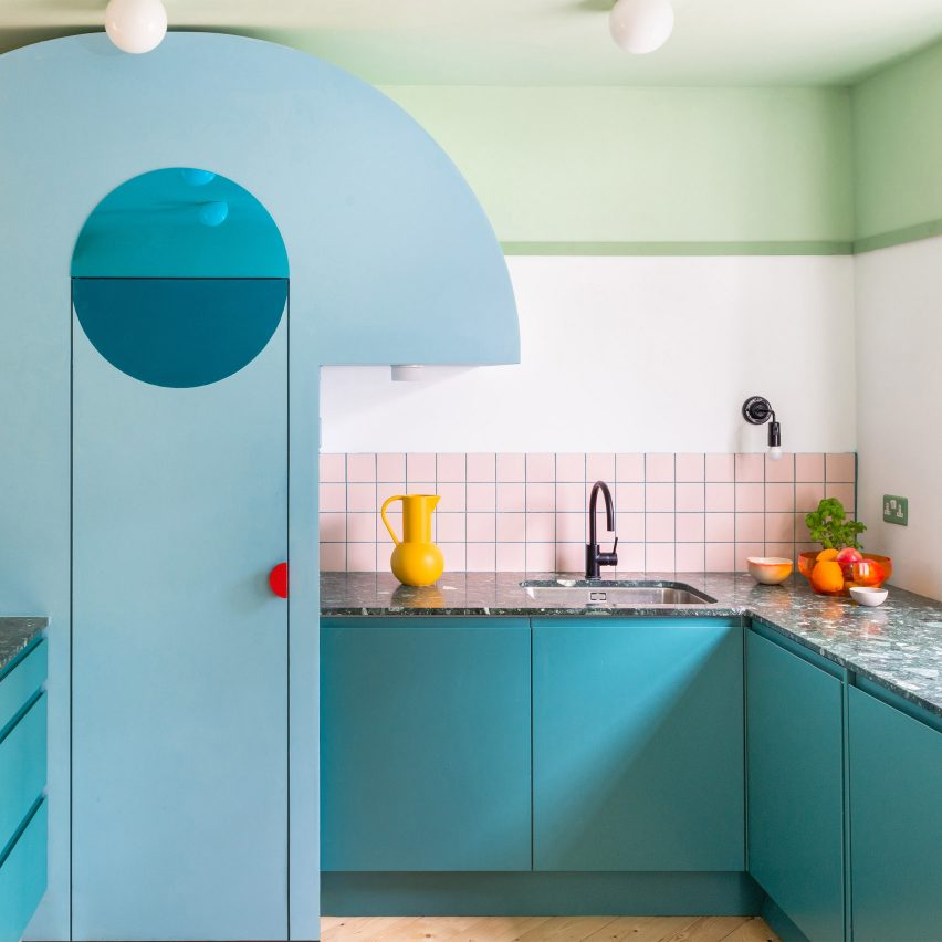 A colourful kitchen with blue cabinetry and pink tiles