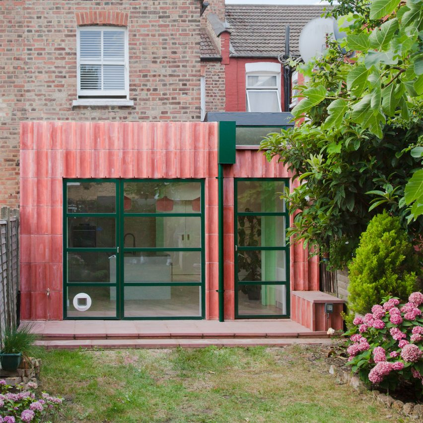 A pink-hued concrete extension with green detailing