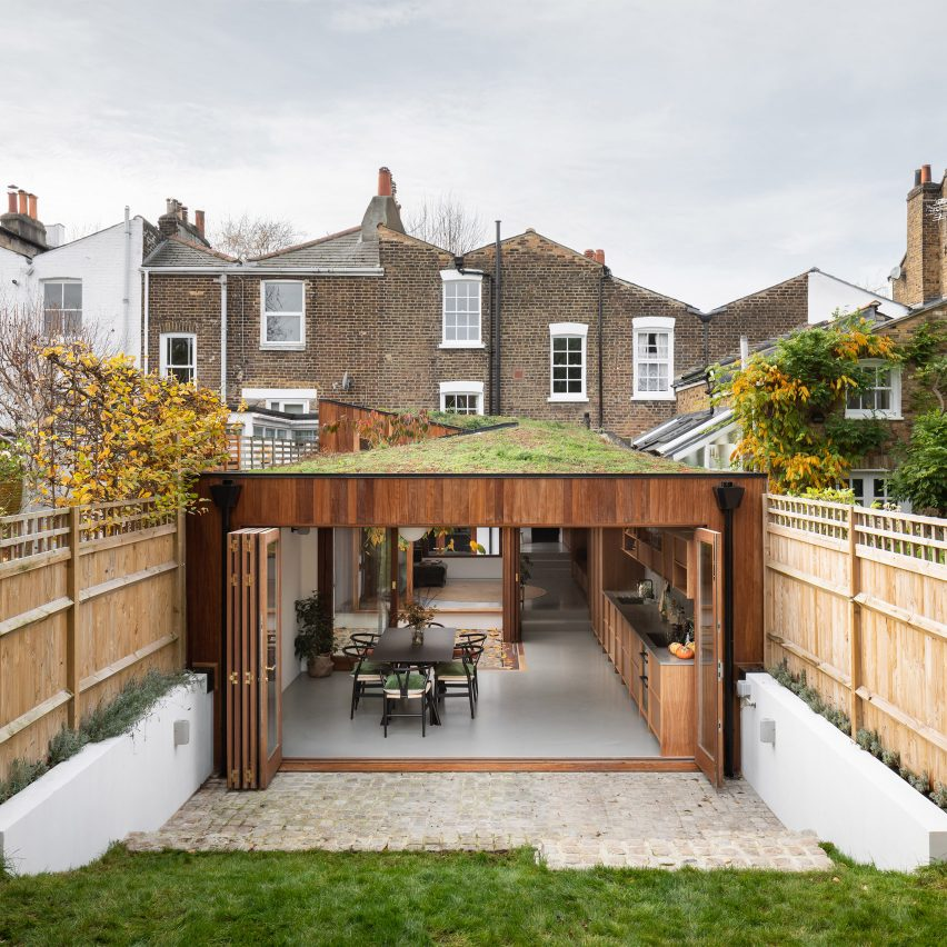A wood-clad house extension with a green roof