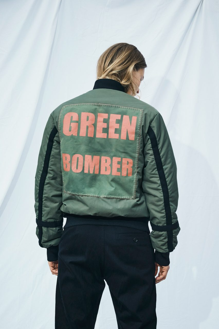 Green bomber jacket with photosynthetic applique and slogan print