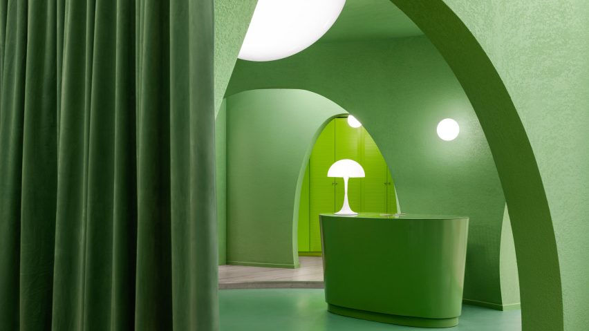 The space has green curtains and green furnishings