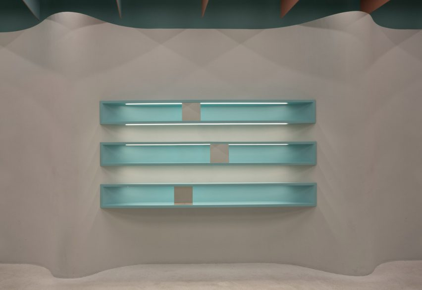 Built-in turquoise shelves in undulating plaster wall of Eyewa store interior