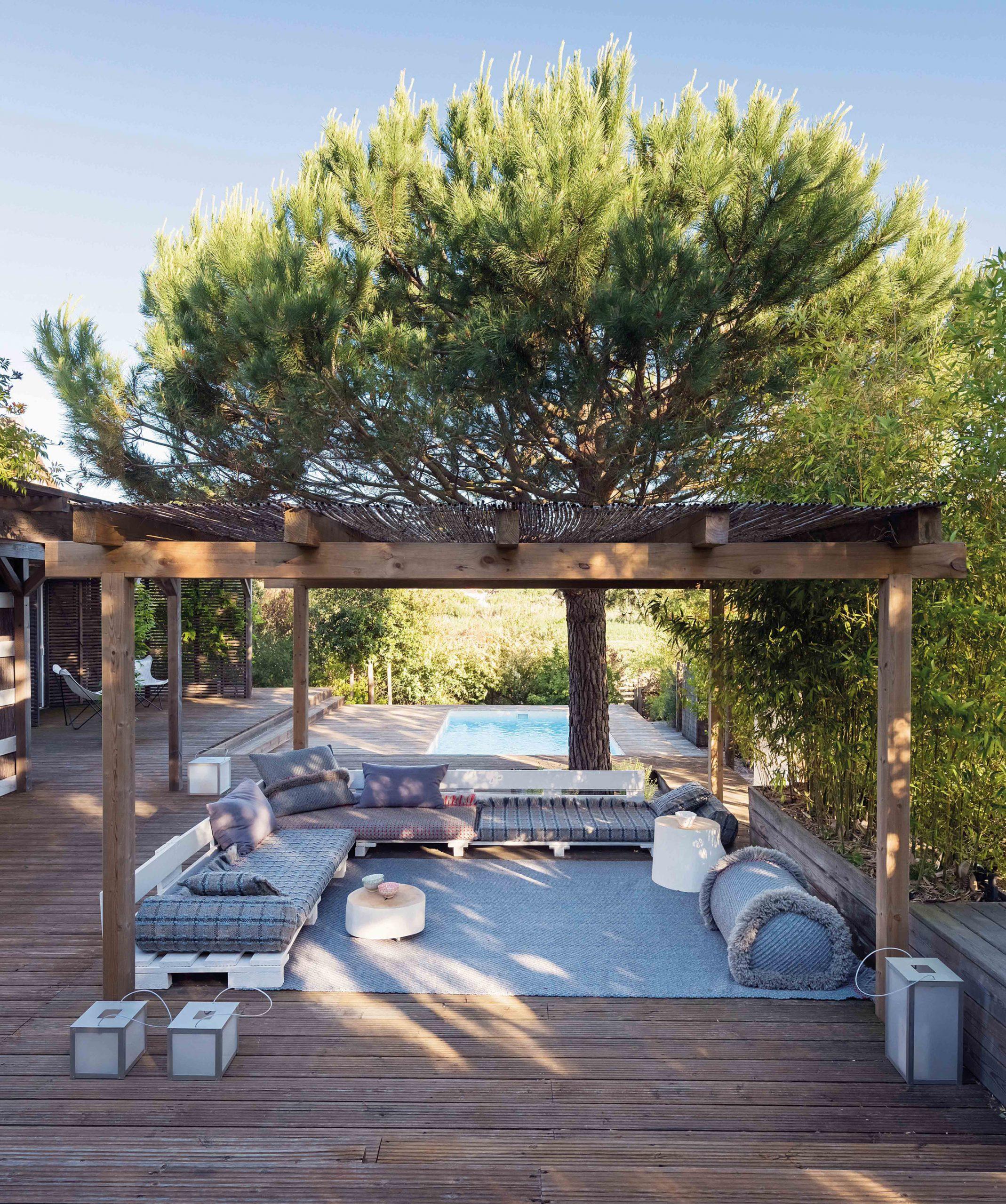 Blue outdoor furniture under a pergola by Patricia Urquiola
